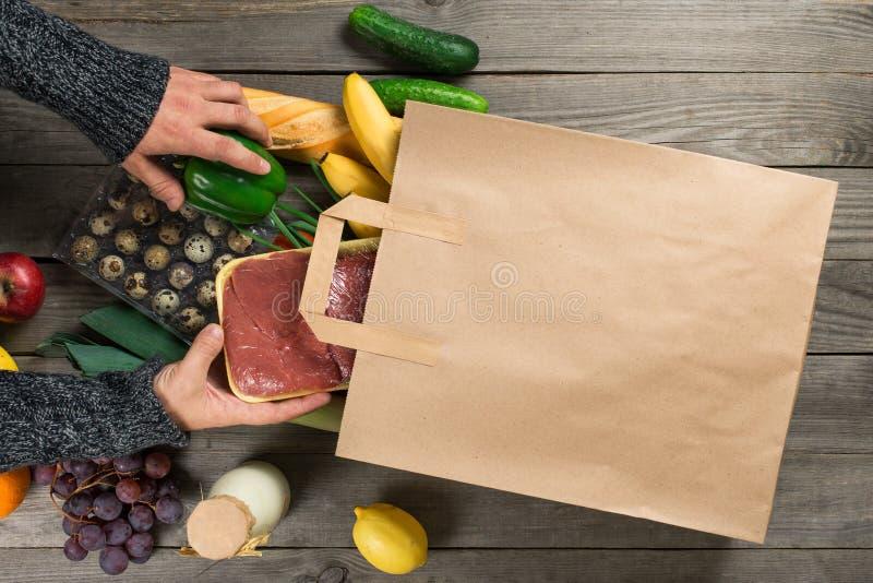 Verschillend gezond voedsel op houten lijst met document zak royalty-vrije stock afbeelding