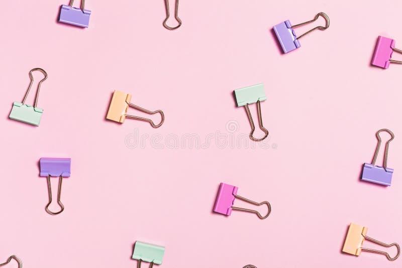 Verschillend helder paperclippatroon op roze achtergrond stock foto's