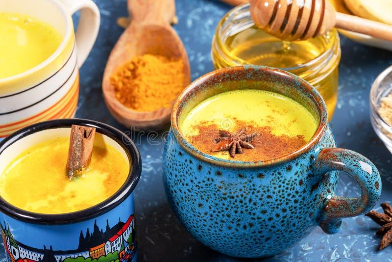 Verschillende bekers met gouden kurkmelk, kurkpoeder en honing op een blauwe, getextureerde achtergrond Sluiten, selectieve focus stock foto's