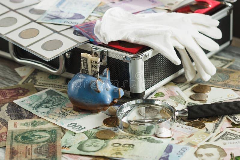 Verschillende collector` s muntstukken en bankbiljetten in de doos met stock foto's