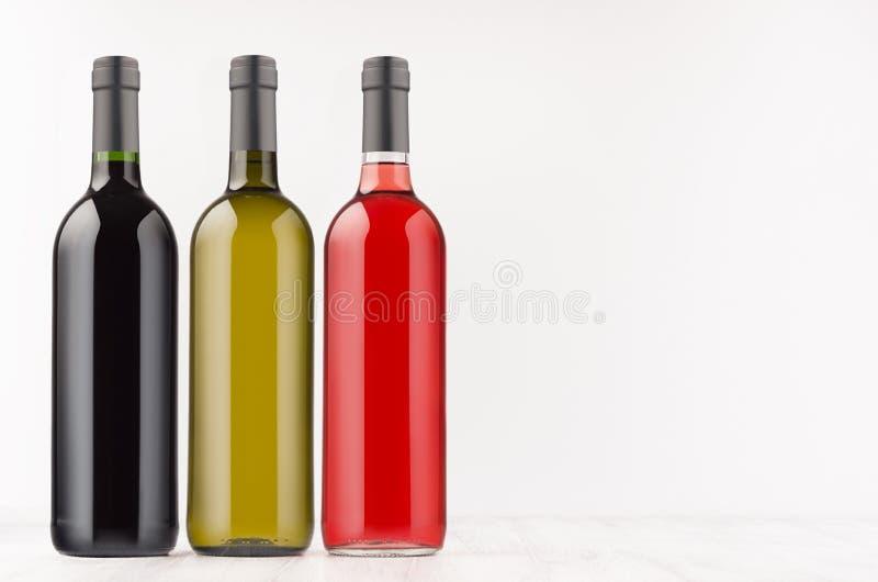 Verschillende de inzameling van wijnflessen kleurt omhoog - rood, groen, zwart op witte houten raad, spot, exemplaarruimte royalty-vrije stock foto