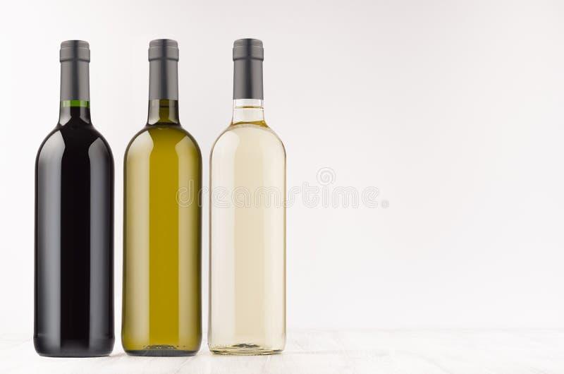 Verschillende de inzameling van wijnflessen kleurt omhoog - transparant, groen, zwart op witte houten raad, spot, exemplaarruimte royalty-vrije stock afbeelding