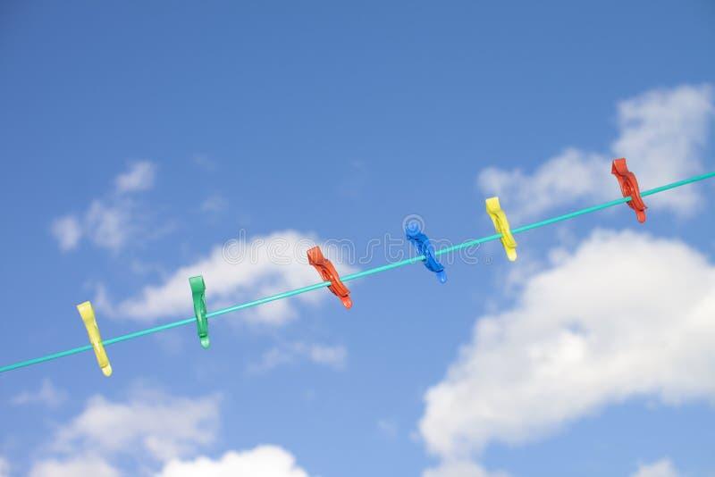 Verschillende gekleurde wasknijpers op een lijn van de waslijn stock afbeelding
