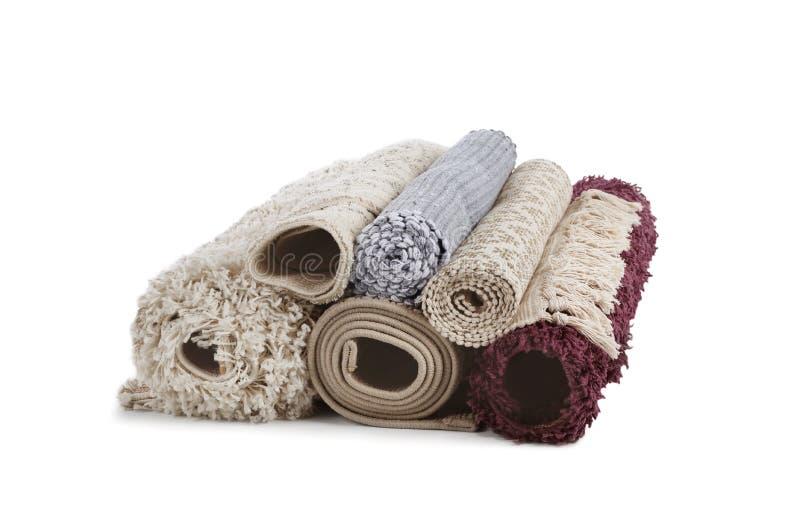Verschillende gerolde tapijten op witte achtergrond stock afbeeldingen