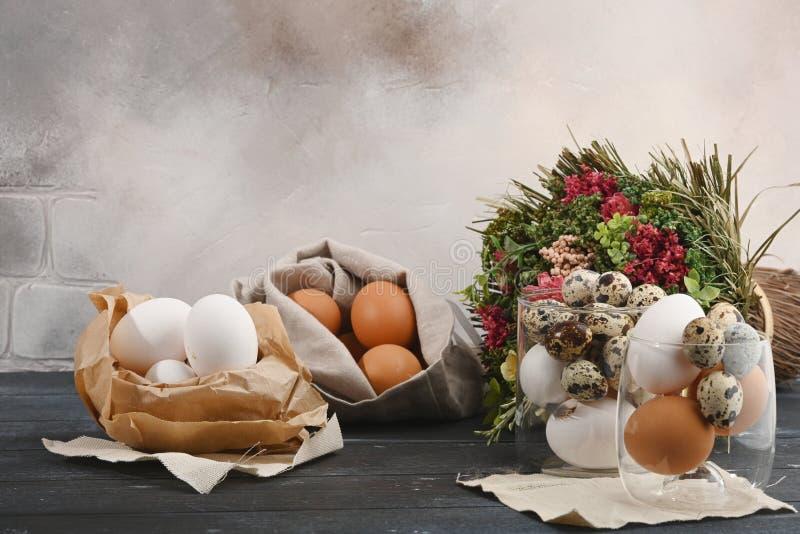 Verschillende groottekwartels en kippeneieren op een houten oppervlakte stock foto