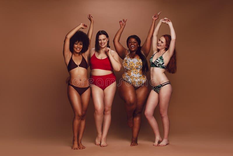 Verschillende groottevrouwen in bikinis die samen dansen stock fotografie