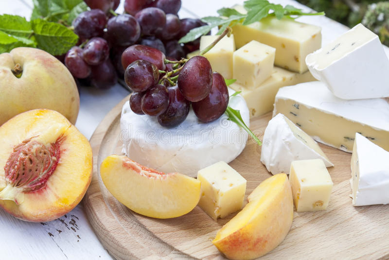 Verschillende heerlijke kazen en vruchten op houten ronde raad royalty-vrije stock foto