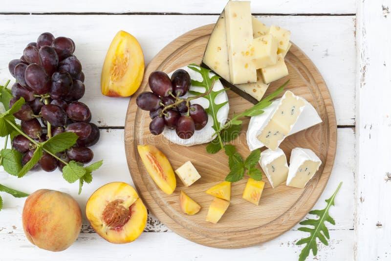 Verschillende heerlijke kazen en vruchten op houten ronde raad stock fotografie