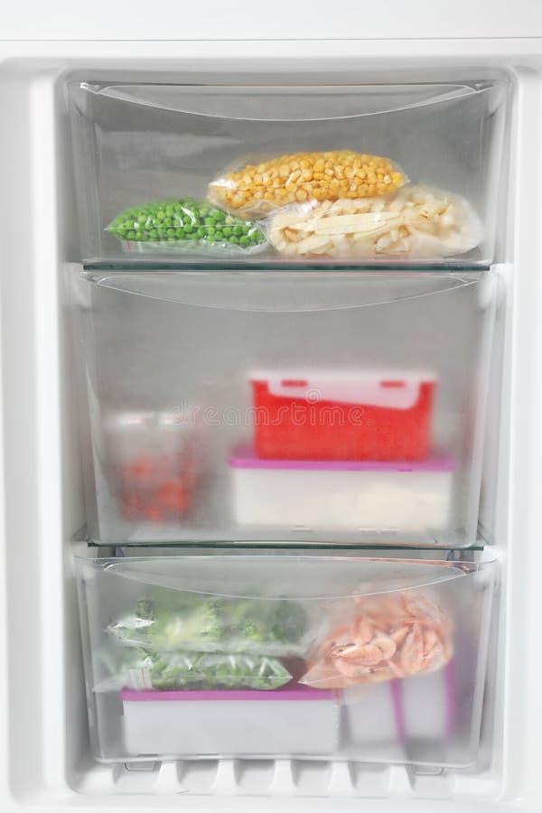 Verschillende ingepakte bevroren producten in ijskast stock foto's