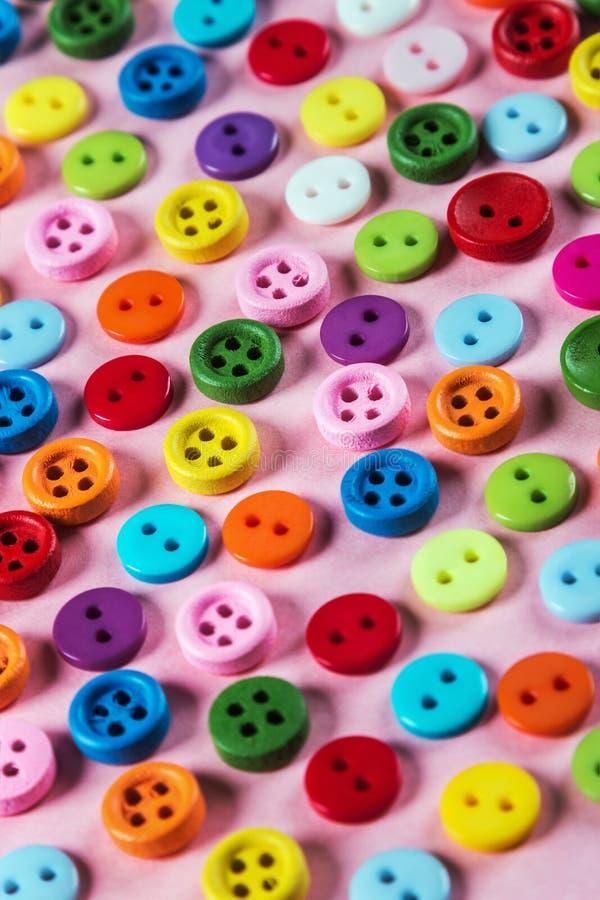 Verschillende kleurenknopen op roze achtergrond royalty-vrije stock fotografie