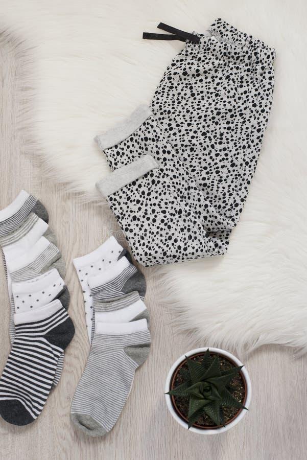 Verschillende kleurensokken en grijze broek op een grijze houten vloer, een bonttapijt en een installatie Het winkelen concept stock foto's