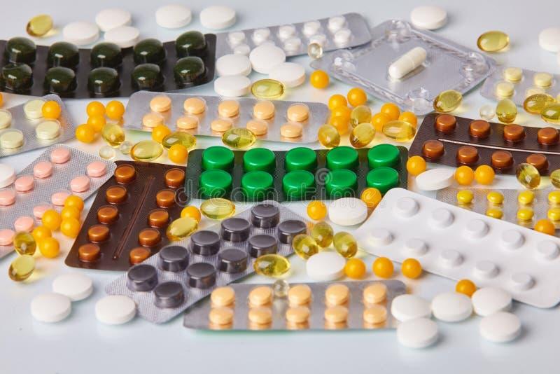Verschillende kleurrijke pakken pillen en tabletten op witte achtergrond stock afbeelding