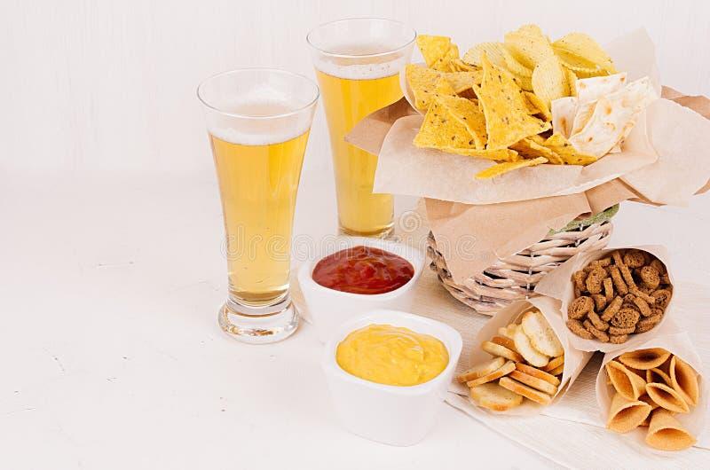 Verschillende kruidige Mexicaanse snacks en sausen - ketchup, kerrie - in kom, koud lagerbierbier op witte houten raad stock afbeeldingen