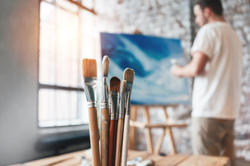 Verschillende kunstenaarspenselen clouseup op achtergrond van schilder dichtbij canvas op de schildersezel Tekeningsworkshop Crea stock foto's