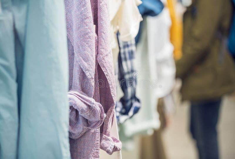 Verschillende Mensenoverhemden die binnen de Kledingsopslag hangen royalty-vrije stock foto