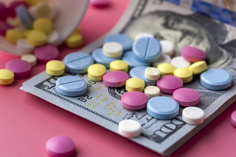 Verschillende Multicolored Pillen op Honderd Dollarsrekeningen stock afbeeldingen