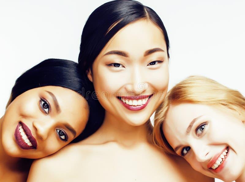 Verschillende natievrouw: Aziaat, Afrikaans-Amerikaan, Kaukasisch samen geïsoleerd bij het witte gelukkige divers glimlachen als  stock fotografie