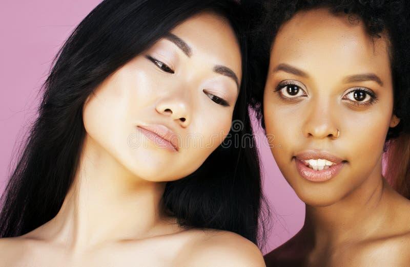 Verschillende natievrouw: Aziaat, Afrikaans-Amerikaan, Kaukasisch samen geïsoleerd bij het witte gelukkige divers glimlachen als  stock foto's