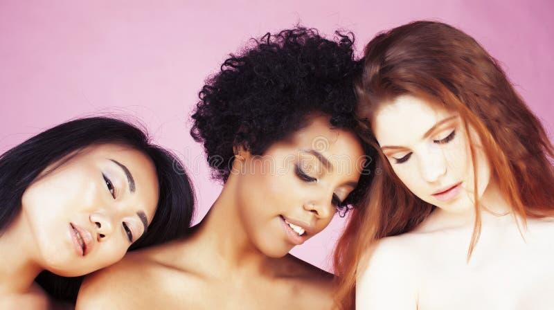 Verschillende natievrouw: Kaukasische Afrikaans-Amerikaan, Aziaat samen bij het roze gelukkige glimlachen als achtergrond, divers stock fotografie