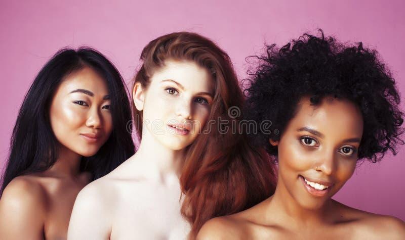 Verschillende natievrouw: Kaukasische Afrikaans-Amerikaan, Aziaat samen bij het roze gelukkige glimlachen als achtergrond, divers royalty-vrije stock fotografie