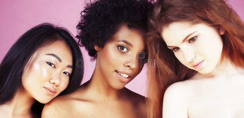 Verschillende natievrouw: Kaukasische Afrikaans-Amerikaan, Aziaat samen bij het roze gelukkige glimlachen als achtergrond, divers stock afbeeldingen