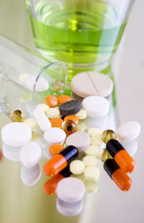 Verschillende pillen en geneesmiddelen op een spiegeloppervlakte royalty-vrije stock afbeeldingen