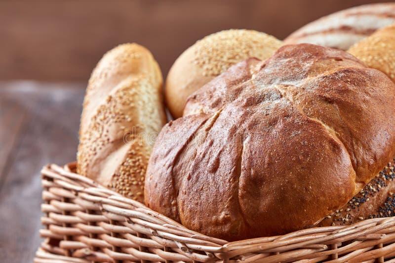 Verschillende soorten Brood in een rieten mand op een houten achtergrond stock foto