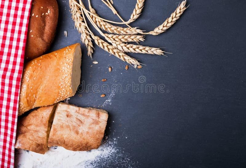 Verschillende soorten brood, tarwe en bloem op zwarte backgroun stock afbeelding