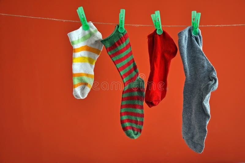 Verschillende soorten het gestreepte sokken hangen geïsoleerd op rood stock foto's