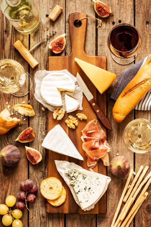 Verschillende soorten kazen, wijn, baguette, vruchten en snacks stock afbeelding