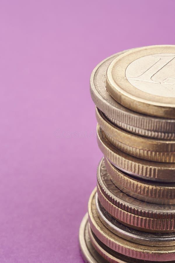 Verschillende soorten muntstukken over een purpere achtergrond Macrodetail stock foto