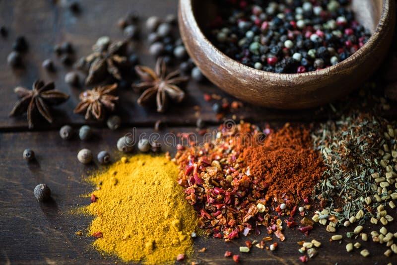 Verschillende soorten peper in kom en kruiden met verspreide kruiden royalty-vrije stock foto