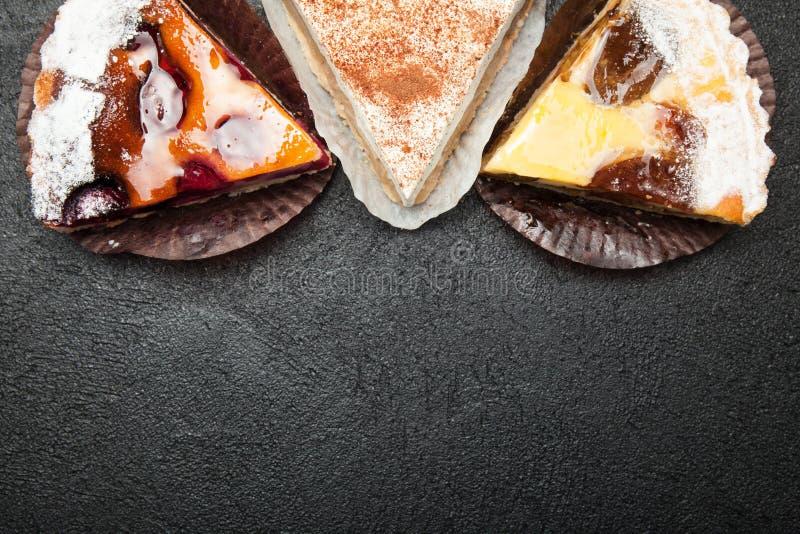 Verschillende soorten zoete eigengemaakte gebakjes op een zwarte achtergrond, lege ruimte voor tekst stock foto's