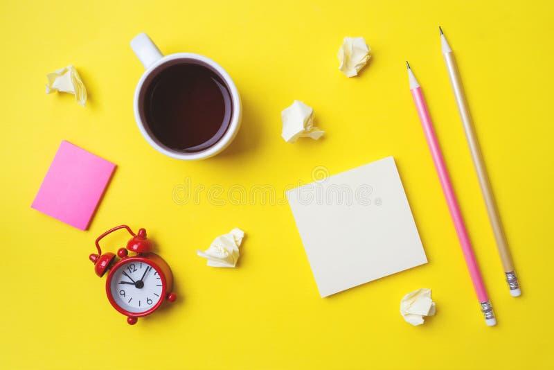 Verschillende stickerskantoorbehoeften, een Kop van koffie en een klok op een gele lijst met een exemplaar van ruimte Het onderwi stock fotografie