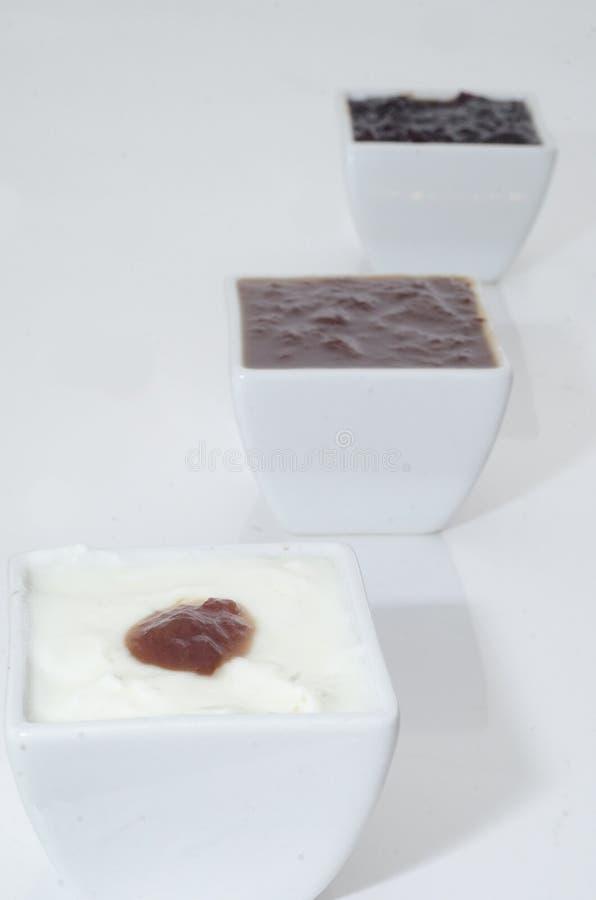 Verschillende tipes van jam in witte kommen stock afbeeldingen