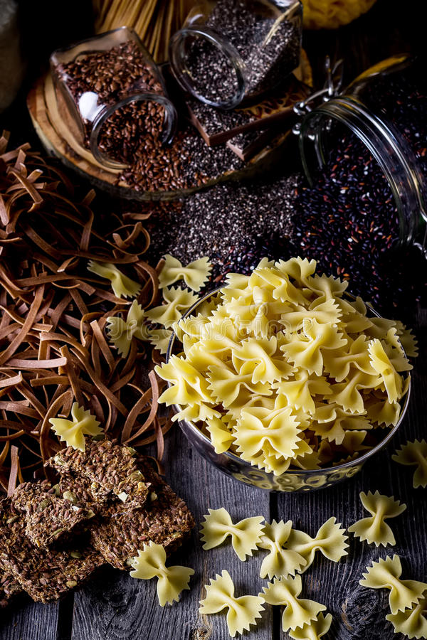Verschillende types van deegwaren, rijst, zaden van vlas en chia op donkere houten lijst stock fotografie