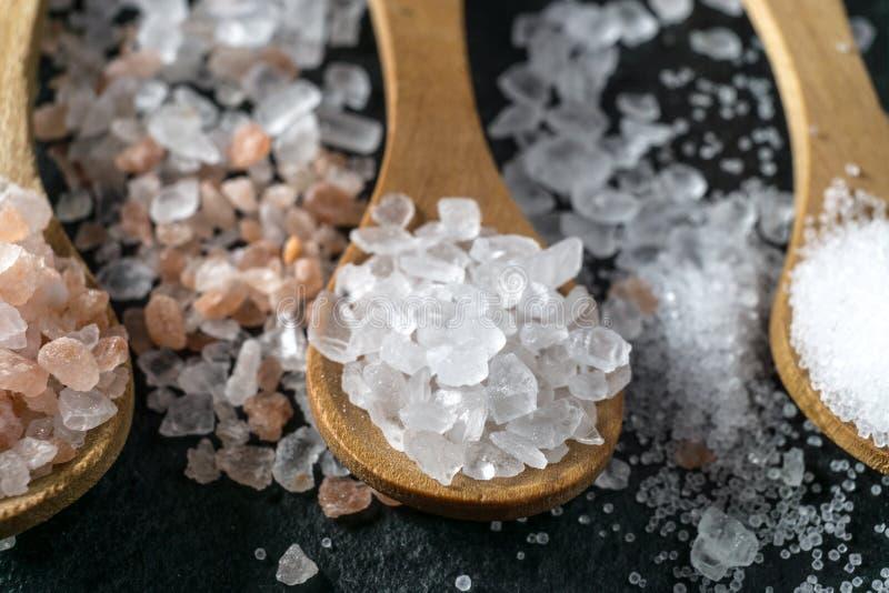 Verschillende types van zout Hoogste mening over drie houten lepels stock afbeeldingen