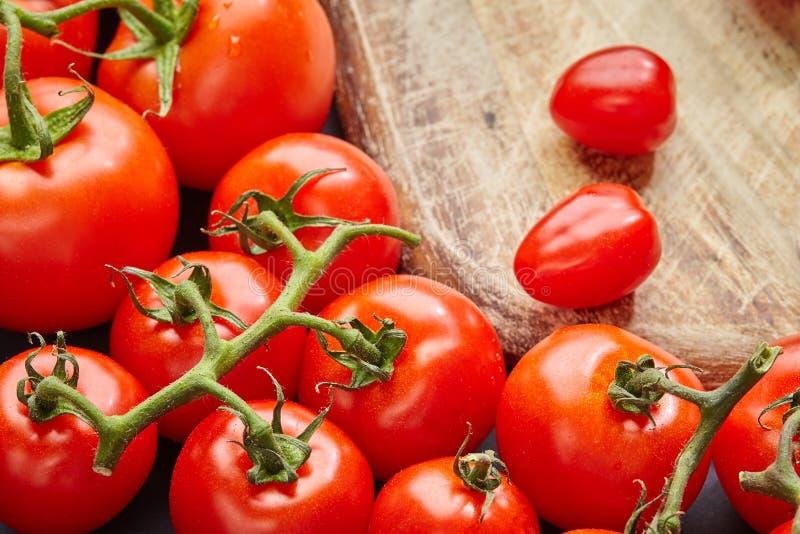 Verschillende verscheidenheden van rijpe tomaten op een houten achtergrond stock foto
