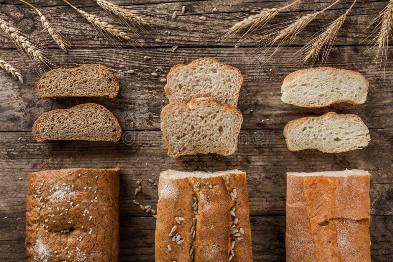 Verschillende verse brood en aartjes van tarwe op rustieke houten achtergrond Creatieve die lay-out van brood wordt gemaakt stock afbeeldingen