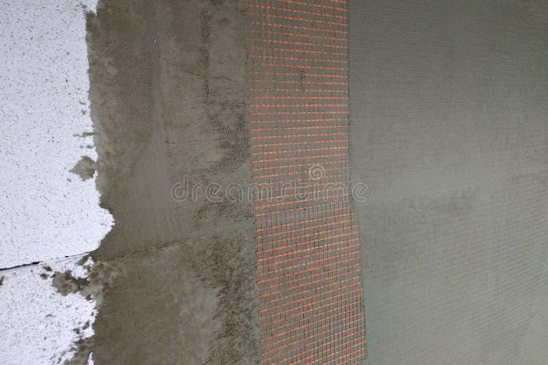 Verschließen der Schichten über Styropor-Isolierung, Maschen, Gips, Zement, Mörtel, Klebstofflösung stockfotografie