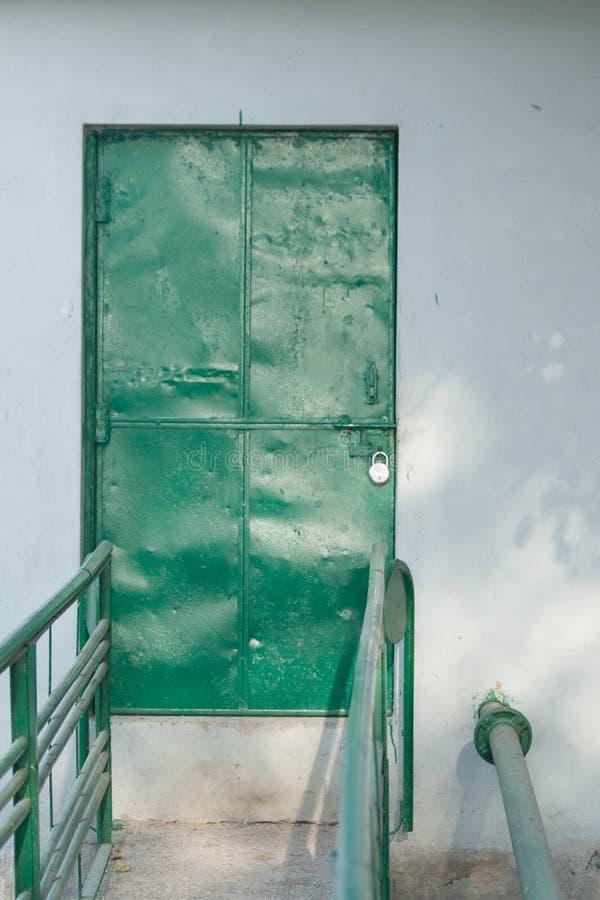 Verschlossene grüne Eisentür stockbild