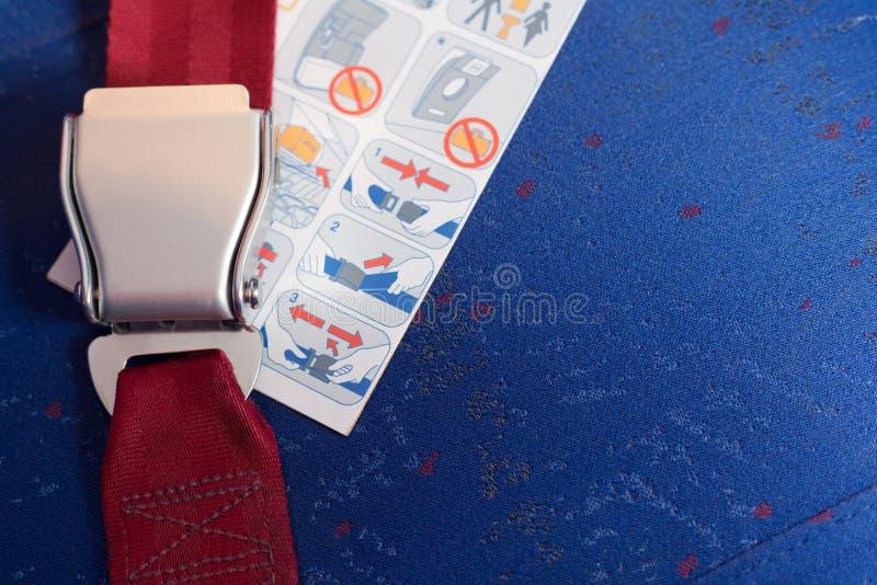 Verschlossener Sicherheitsgurt und Anweisung legen auf den Stuhl. stockfotos