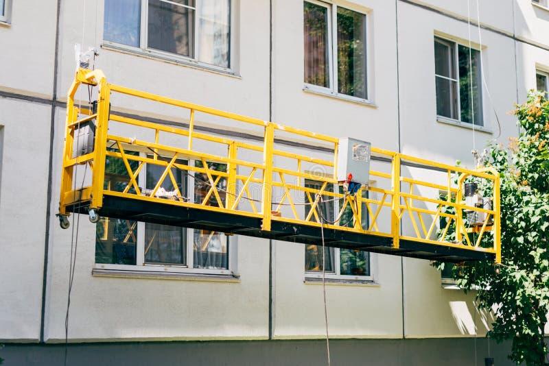 Verschobene Bauwiege Einfassung, Reparatur, Wartung, das Gebäude in der sonnigen Sommerzeit malend lizenzfreie stockfotografie
