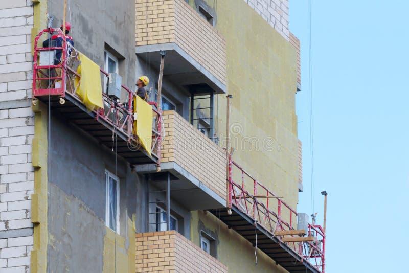 Verschobene Wiege für Arbeitskraft für das Gegenüberstellen der Fassade hohen Gebäudes u lizenzfreies stockbild