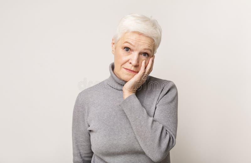 Verschotelde oudere vrouw die wantrouwen hoog in het vaandel stock afbeeldingen
