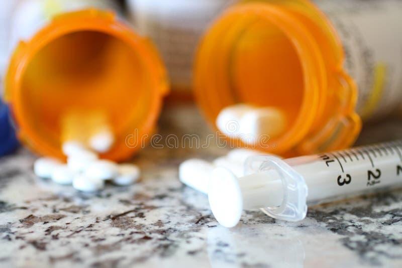 Verschreibflaschen mit Schmerztabletten und Spritze stockbilder