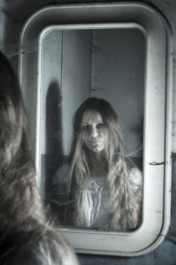 Verschrikkingsmeisje in de spiegel stock afbeeldingen