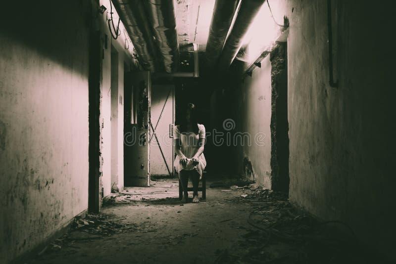 Verschrikkingsscène van een enge vrouw in donkere gang stock fotografie