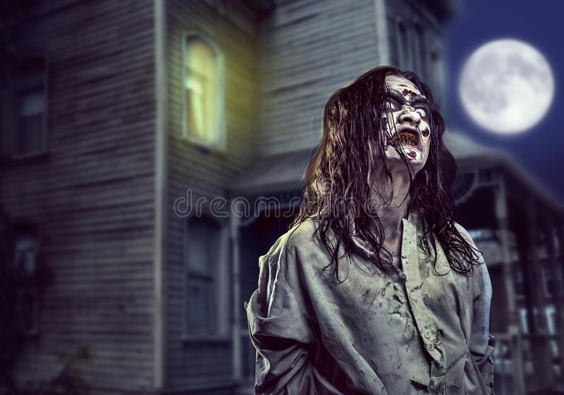 Verschrikkingszombie dichtbij het verlaten huis Halloween stock foto