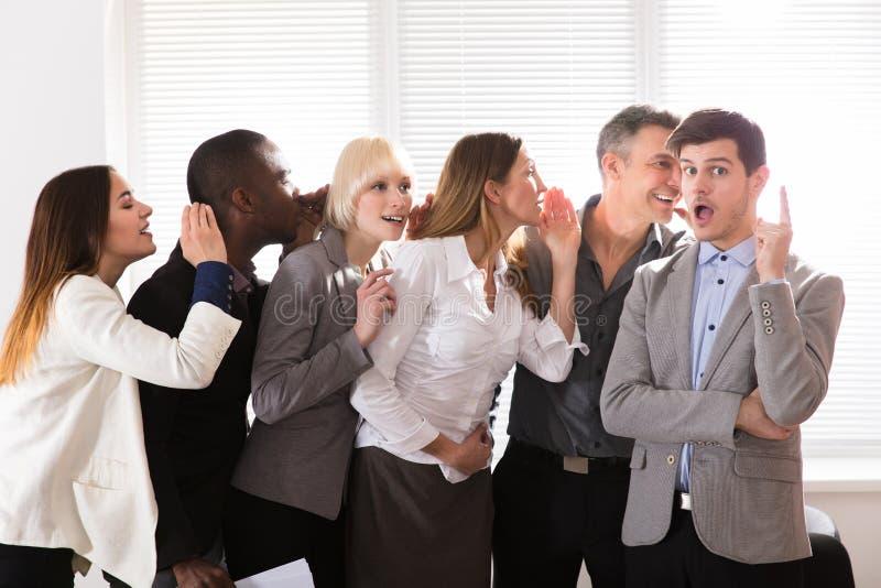 Verschwiegene Geschäftskollegen, die im Büro flüstern stockbilder